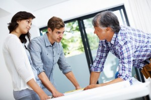 Young couple discussing home plan on blueprint with architect